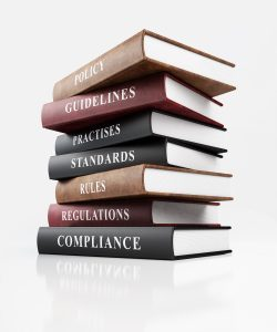 Policy, guidelines, regulations, standards leather covered books stacked.