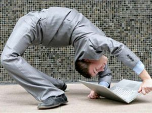 Information technologist doing backbend to look at computer as agile project management visual.