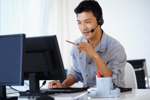 Shot of an Asian man using a computer and talking on a headset