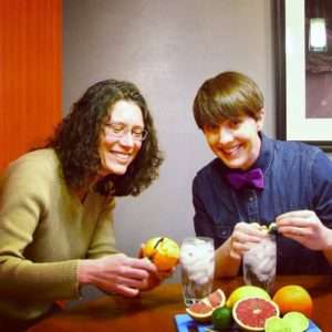 2 instructional designers surrounded by fruit, putting citrus twists into glasses of ice water